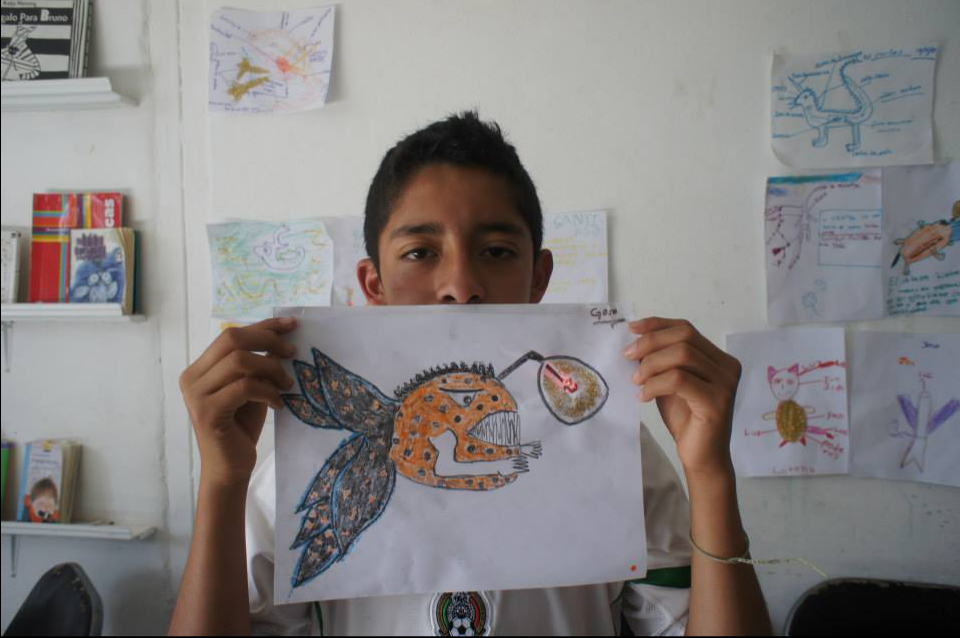 A child holding a drawing with an LED light in it.