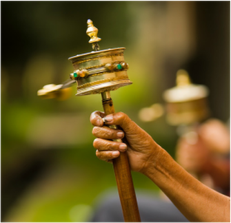 A Tibetan prayer wheel which has a rotating disc on a graspable stick.